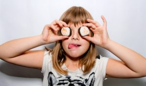 Young Girl with sushi in hands near eyes