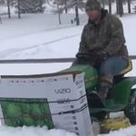Innovative Man Creates Snow Plow By Attaching A Recycled TV Box To Lawn Mower